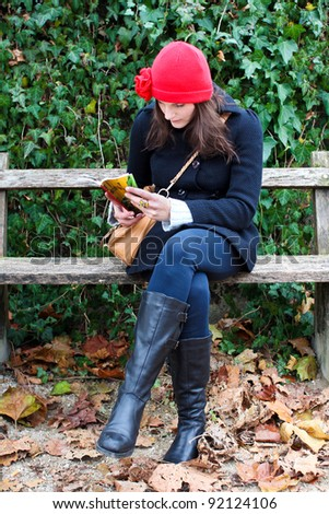 Woman Sitting On A Bench And Reading A Book, clothed in warm winter clothing