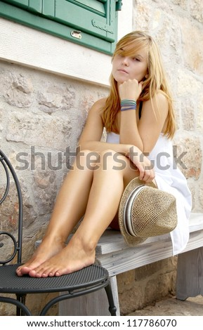 Woman sitting on a bench at the stone building