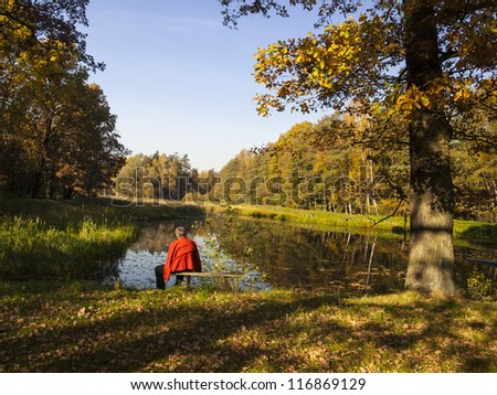 Woman sitting on a bench by the pond in the park on a sunny autumn day