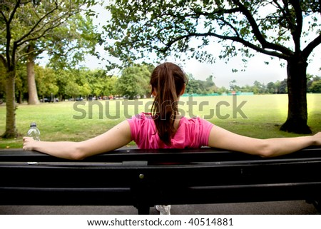 woman sitting on a bench looking at a landscape
