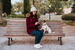 woman sitting on a bench, using mobile phone in a park with her adorable jack russell dog. Lifestyle outdoors