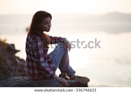Woman sitting on a sand beach in front of sunset and ocean or lake in autumn