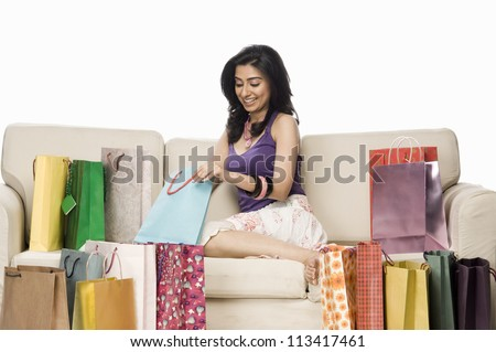 Woman sitting on a sofa and holding a shopping bag