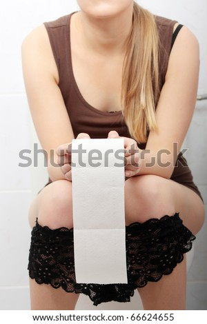 Woman sitting on a toilet holding toilet paper. Stomach issues concept.