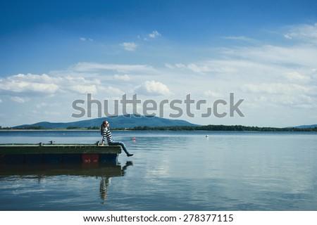 Woman sitting on a wooden jetty enjoying the sunshine.