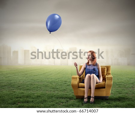 Woman sitting on an armchair on a green meadow and holding a balloon with cityscape on the background