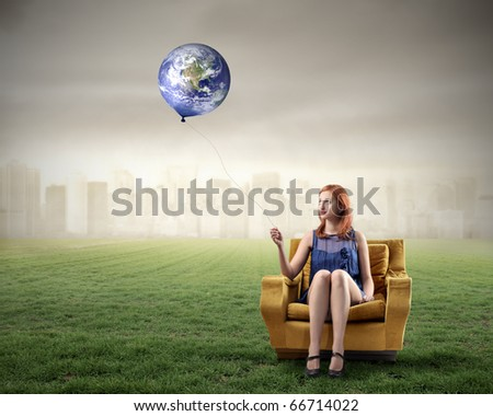 Woman sitting on an armchair on a green meadow and holding the Earth like a balloon with cityscape on the background