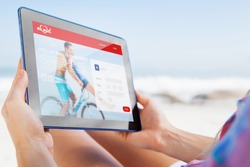 Woman sitting on beach in deck chair using tablet pc against dating website