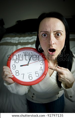 woman sitting on bed with clock shocked at being late for work