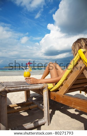 Woman sitting on deckchair and enjoying a cocktail on a tropical beach