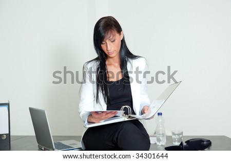Woman sitting on desk holding ring binder while looking at sales numbers for success business