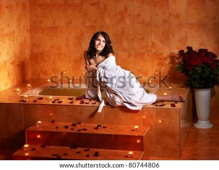Woman sitting on edge of bath tub.