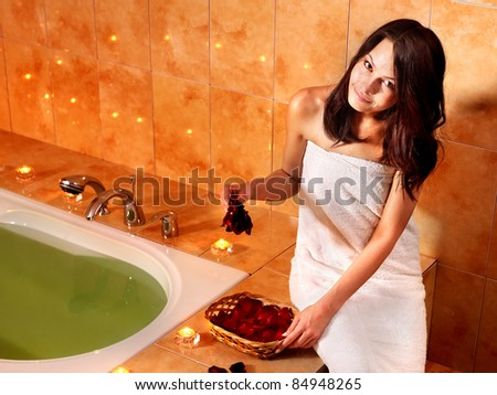 Woman sitting on edge of bath tub.