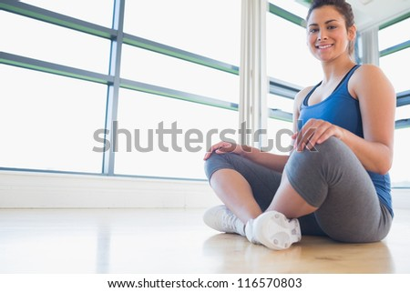 Woman sitting on floor and smiling in fitness studio - stock photo