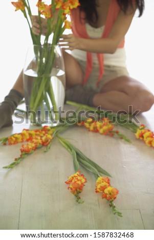 Woman sitting on floor arranging flowers in vase