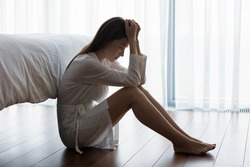 Woman sitting on floor feels unhappy by personal problems, break up or ruined marriage, unwilling pregnancy regret about abortion decision, chronic insomnia sleep disorder, alcohol dependence concept