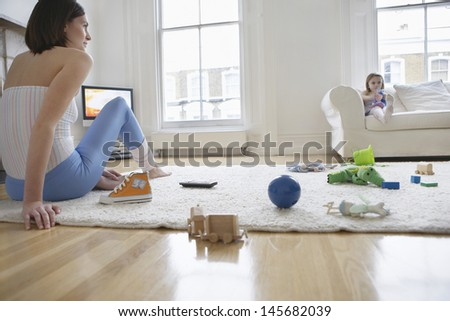 Woman sitting on floor surrounded with toys and daughter on sofa