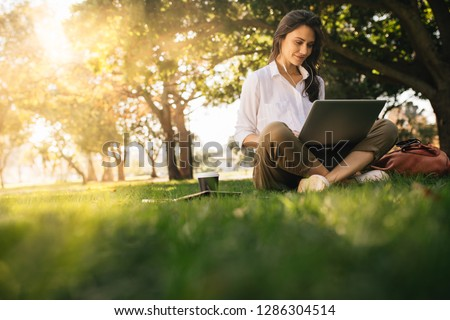 Woman sitting on grass at park working on laptop. Female wearing earphones using laptop while sitting under a tree at park with bright sunlight from behind.