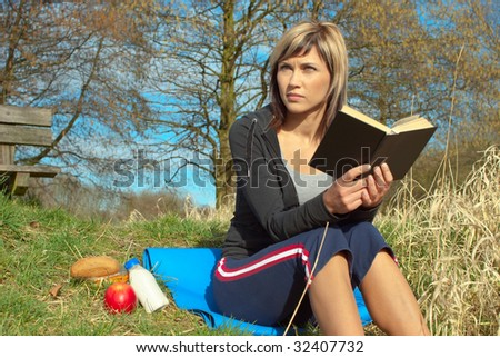 Woman sitting on grass reading a book.