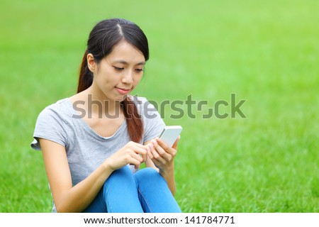 Woman sitting on grass with smartphone