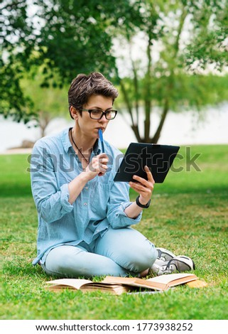Woman sitting on green grass and studying online on tablet