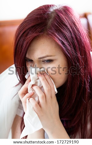 Woman sitting on her bed and blowing nose