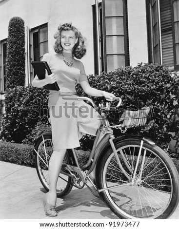 Woman sitting on her bicycle with a book in her arms