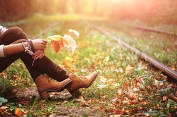 woman sitting on rail trails and holding colorful autumn leaves.  natural vintage background