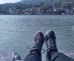 woman sitting on shore of river  - Rishikesh