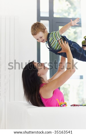 woman sitting on sofa and lifting up his son
