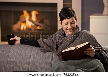 Woman sitting on sofa at home on a cold winter day, reading book.?