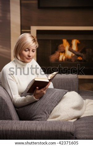 Woman sitting on sofa at home reading book, looking down.