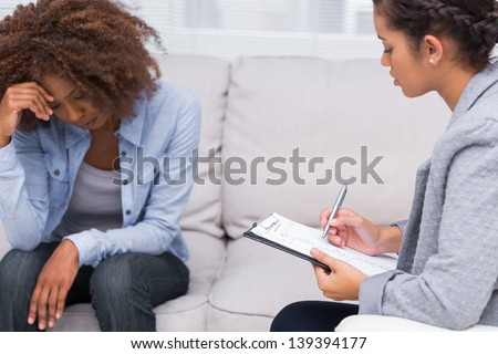 Woman sitting on sofa at therapy with doctor taking notes