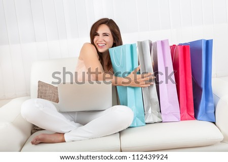 Woman Sitting On Sofa Holding Shopping Bag At Home