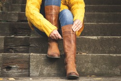 Woman sitting on stairs and fasten zipper on her leather boots. Autumn fashion concept
