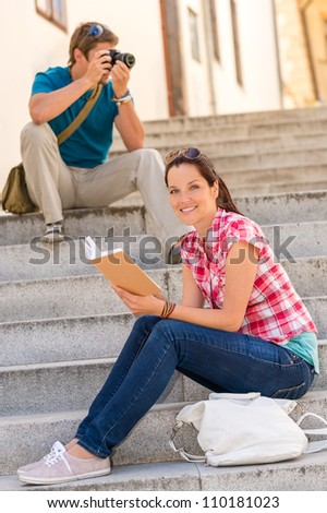 Woman sitting on stairs reading a book man photographing camera