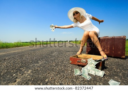 Woman  sitting on suitcase with cash stops the car on countryside road