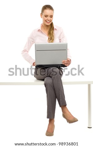 Woman sitting on table with laptop