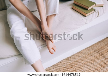 Woman sitting on the bed massages her foot, close-up. Woman with a slender body massages the leg, Young woman massaging her foot on the white bed after training or hard working day. Healthcare concept Stockfoto ©