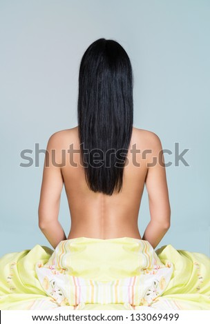 Woman sitting on the bed with back toward camera, light background