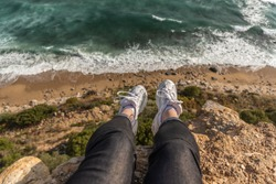 Woman sitting on the cliff above the sea. First person point of view, legs.