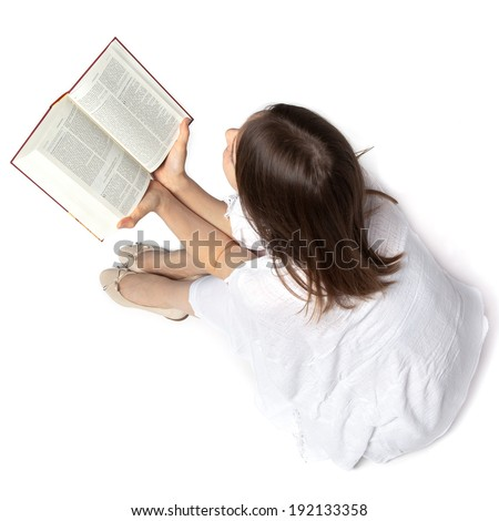 Woman sitting on the floor and reading a Bible from above