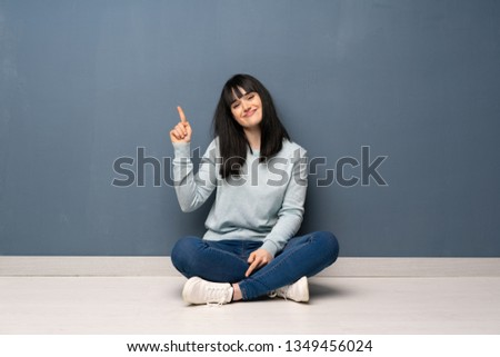 Woman sitting on the floor showing and lifting a finger in sign of the best