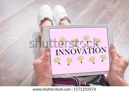 Woman sitting on the floor with a tablet showing innovation concept