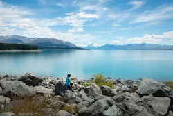 Woman sitting on the shore of Lake Pukaki, enjoying the views of Mt Cook and Southern Alps, South Island.