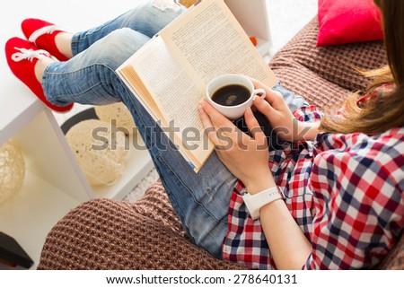 Woman sitting on the sofa reading a book holding her coffee mug in living room at home #278640131