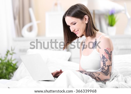 Woman sitting on the sofa with the laptop
