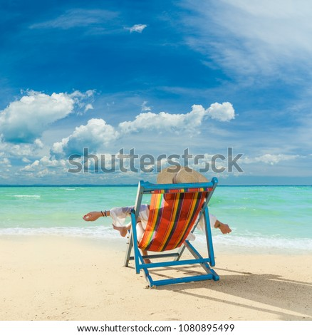 Woman sitting on the wild beach of the island of Lefkada in Greece  #1080895499