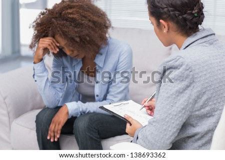Woman sitting on therapists couch looking down with therapist taking notes