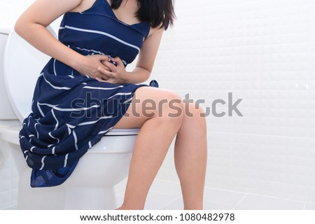 Woman sitting on toilet with diarrhea or constipated pain concept